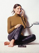 Young woman sitting by wall, using telephone