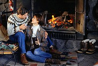 Couple sitting in ski lodge by fireplace, woman holding insulated flask