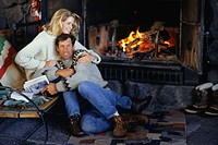 Couple sitting in ski lodge by fireplace, embracing
