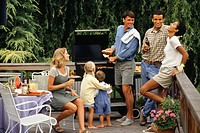 Two couples and two children (2-3) (4-5) barbecuing on patio