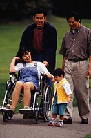 Family and baby boy (18-24 months) walking in park, mother in wheelchair