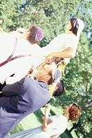 Men carrying bride on chair at wedding ceremony
