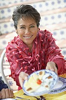 Portrait of a mature woman holding up a plate of food