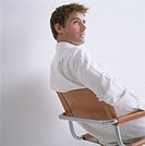 Man wearing white shirt, sitting on chair