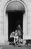 Women sitting on steps watching passers by (B&W)