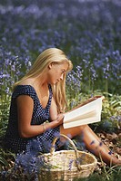 Woman reading book in meadow, close-up