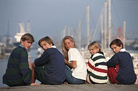 Children (8-17) sitting by harbour, rear view