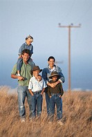 Family with three children (6-9) in field, portrait