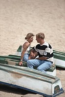 Young couple sitting on canoe at beach