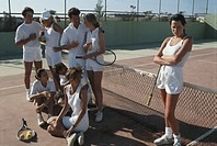 Group of tennis players in court, woman standing away