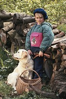 Girl (6-7) with dog in forest, smiling