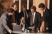 Five businessmen standing around woman using landline phone