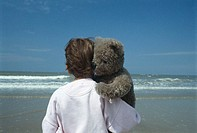 Child with teddy bear on beach, rear view