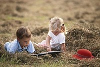 Boy and girl (2-5) reading in farm
