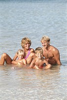 Parents with children (4-7) sitting in ocean, smiling