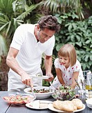 Father serving daughter (3-5) from table, outdoors