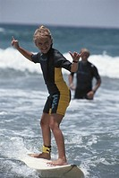 Girl (8-11) surfboarding, father in background