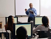 Mature male professor reading from book at front of classroom