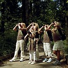 Six girls (5-11) on footpath in forest, looking through binoculars