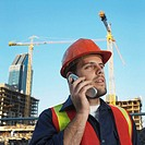 Male construction worker using mobile phone, looking away