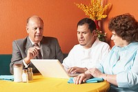 Portrait of a businessman with a businesswoman and a chef looking at a laptop