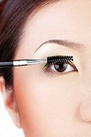 Woman applying mascara on her lashes