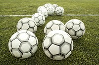 Footballs on pitch by white line (focus on foreground)