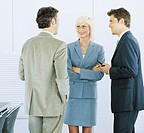 Businesswoman standing with two businessmen, smiling