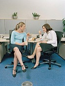 Two female work colleagues taking break at desks, smiling and laughing