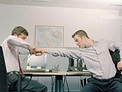Two male work colleagues play fighting in office with rulers