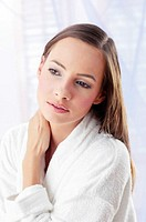 Woman in bathrobe staring blankly at a space