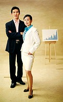 Businessman and businesswoman posing near a chart.
