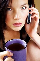 Woman holding a cup of coffee while talking on the handphone