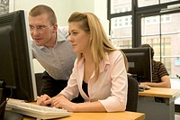 Male teacher helping young female student at computer
