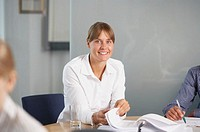 Young woman at table looking through file, smiling, portrait