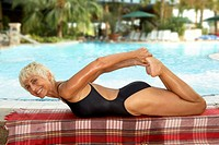 Mature woman stretching by pool, lying on stomach, smiling, portrait