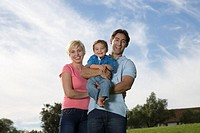 Parents and toddler son (21-24 months) outdoors, smiling, portrait