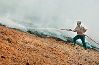 Firemen fighting a brush fire in the Atlanta area with water and saftey equipment