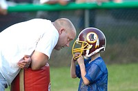 Coach talking to kid at football practive about game and learning rules