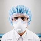 Portrait of male technician in protective gear and face mask in lab