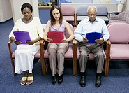 Group of people reading paperwork while sitting in waiting room