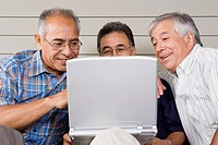 Three elderly men with laptop