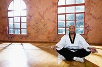 Mature man meditating on floor in karate uniform