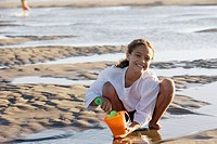 Portrait of girl filling bucket with water at beach