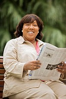Portrait of woman sitting on bench reading newspaper