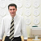 Businessman with time zone clocks on the wall behind him