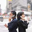 Two businesswomen standing while talking on cell phone