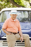 Portrait of elderly man leaning on old pickup truck