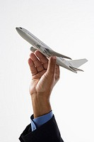 Close up of hand holding toy airplane in air