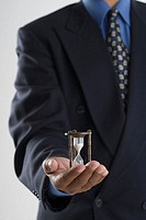 Close up of businessman's hands holding hour glass